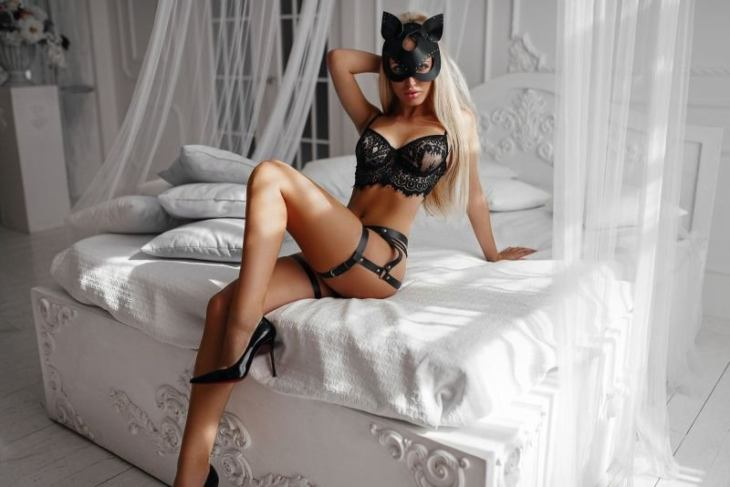 women blonde brunette in bed sitting high heels mask